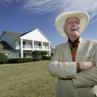 Photo - FILE - In this Oct. 9, 2008, file photo, the late Actor Larry Hagman poses in front of the  Southfork Ranch mansion made famous in the television show,