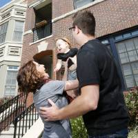Photo - Kate  and Kyle Jones play with their 10-month-old daughter, Ramsey Jones, outside of their Deep Deuce home at The Hill in downtown Oklahoma City. Photo by Nate Billings, The Oklahoman