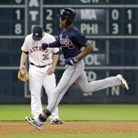 Photo - Atlanta Braves' B.J. Upton, right, runs past Houston Astros third baseman Matt Dominguez (30) after hitting a home run during the third inning of a baseball game Tuesday, June 24, 2014, in Houston. (AP Photo/David J. Phillip)