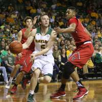 Photo - Baylor guard Brady Heslip (5) is pressured by Texas Tech Jordan Tolbert (32) during the first half of an NCAA college basketball game, Saturday, March, 1, 2014, in Waco, Texas. (AP Photo/Waco Tribune Herald, Michael Bancale)