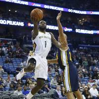 Photo - New Orleans Pelicans forward Tyreke Evans (1) drives to the basket for two of his 22-points as Utah Jazz guard Gordon Hayward (20) defends in the first half of an NBA basketball game in New Orleans, Friday, March 28, 2014. The Pelicans defeated the Jazz 102-95. (AP Photo/Bill Haber)