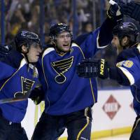 Photo - St. Louis Blues' Alexander Steen, left, is congratulated by teammates David Backes, center, and Steve Ott, right, after scoring the game-winning goal during the third overtime in Game 1 of a first-round NHL hockey Stanley Cup playoff series against the Chicago Blackhawks Thursday, April 17, 2014, in St. Louis. The Blues won 4-3 in triple overtime. (AP Photo/Jeff Roberson)