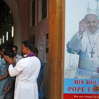 Photo - A boy touches a portrait of Pope Francis put up at the entrance of Saint Mary's Basilica as an Indian Catholic priest blesses devotees after attending a mass in Hyderabad, India, Sunday, March 17, 2013. Argentine's former cardinal Jorge Mario Bergoglio was chosen as leader of the Catholic Church on March 13, 2013, making him the New World's first pope. (AP Photo/Mahesh Kumar A.)