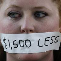 Photo - A silent protester cries while wearing a sticker over her mouth signifying the loss in wages from the right-to-work law in Lansing, Mich., Wednesday, Dec. 12, 2012. Michigan became the 24th state with a right-to-work law after Gov. Rick Snyder signed the bill Tuesday. (AP Photo/Paul Sancya)