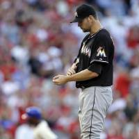 Photo -   Miami Marlins starting pitcher Josh Johnson, right, walks the mound after giving up a two-run home run to Philadelphia Phillies' Jimmy Rollins, left, in the seventh inning of a baseball game on Wednesday, Sept. 12, 2012, in Philadelphia. Philadelphia won 3-1. (AP Photo/Matt Slocum)