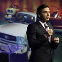 Photo - FILE - In this April 16, 2014 file photo, Ford Motor Company Chief Operating Officer Mark Fields delivers his keynote address at the New York International Auto Show, in New York's Javits Convention Center. Ford says CEO Alan Mulally will retire July 1 and be replaced by Fields. (AP Photo/Richard Drew, File)