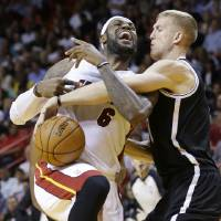 Photo - Miami Heat forward LeBron James (6) is fouled by Brooklyn Nets forward Mason Plumlee as he goes up for a shot during the first half of an NBA basketball game, Tuesday, April 8, 2014 in Miami. (AP Photo/Wilfredo Lee)