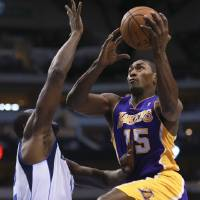 Photo -   Los Angeles Lakers small forward Metta World Peace (15) drives on Dallas Mavericks' Elton Brand (42) during the first half of an NBA basketball game on Saturday, Nov. 24, 2012, in Dallas. (AP Photo/Michael Mulvey)
