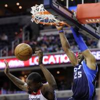 Photo - Dallas Mavericks guard Vince Carter (25) dunks over Washington Wizards forward Martell Webster (9) during the first half of an NBA basketball game, Tuesday, Jan. 1, 2013, in Washington. (AP Photo/Nick Wass)