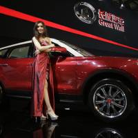 Photo - FILE - In this Saturday, April 20, 2013 file photo, a model poses with a Great Wall H7 SUV at the Shanghai International Automobile Industry Exhibition (AUTO Shanghai) media day in Shanghai, China. SUV sales in China rose 20 percent last year to 2.5 million vehicles, more than double the 8 percent growth of the overall auto market, according to LMC Automotive. SUVs made up 18 percent of all vehicles sold.  Great Wall Motor Co., has become the Chinese industry's breakout success on the strength of its SUVs. The company, headquartered in Baoding, an industrial city southwest of Beijing, said SUV sales in the first three months of the year rose 95 percent over a year earlier and accounted for half the 180,000 vehicles it sold. (AP Photo/Eugene Hoshiko, File)