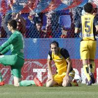 Photo - Atletico de Madrid's goalkeeper Thibaut Courtois from Belgium, left, and Diego Godin from Uruguay, center, stay on the ground after Levante scored a second goal during a Spanish La Liga soccer match at the Ciutat de Valencia stadium in Valencia, Spain, on Sunday May 4, 2014. (AP Photo/Alberto Saiz)