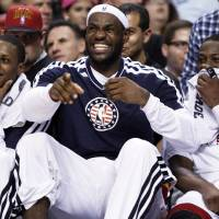 Photo -   Miami Heat forward LeBron James, center, laughs with guards Mario Chalmers, left, and Dwyane Wade as they sit on the bench during the end of the second half of an NBA basketball game against the Brooklyn Nets, Wednesday, Nov. 7, 2012 in Miami. The Heat defeated the Nets 103-73. (AP Photo/Wilfredo Lee)
