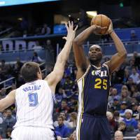 Photo - Utah Jazz center Al Jefferson (25) shoots over Orlando Magic center Nikola Vucevic (9) during the first half of an NBA basketball game, Sunday, Dec. 23, 2012, in Orlando, Fla. (AP Photo/Scott Iskowitz)