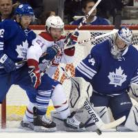 Photo - Toronto Maple Leafs goaltender James Reimer gets hit  in the head as center Nazem Kadri (43) tries to hold off Montreal Canadiens center David Desharnais (51) during the second period of an NHL hockey game in Toronto on Saturday, April 27, 2013. (AP Photo/The Canadian Press, Frank Gunn)