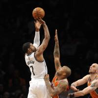 Photo - Brooklyn Nets' Joe Johnson (7) shoots over Phoenix Suns' P.J. Tucker (17) and  Marcin Gortat, right. in the second half of an NBA basketball game on Friday, Jan., 11, 2013 at Barclays Center in New York. The Nets won 99-79. (AP Photo/Kathy Kmonicek)