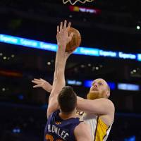 Photo - Los Angeles Lakers center Chris Kaman. back right, drives on Phoenix Suns center Miles Plumlee (22) for a basket in the first half of an NBA basketball game, Sunday, March 30, 2014, in Los Angeles.(AP Photo/Gus Ruelas)