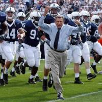 Photo - In this Sept. 4, 2004 file photo, Penn State coach Joe Paterno leads his team onto the field before an NCAA college football game against Akron in State College, Pa. College sports' governing body was expected to deal a series of heavy blows to the Nittany Lions football program on Monday, July 23, 2012, less than two weeks after a devastating report accused coach Joe Paterno and other top university officials of concealing child sex abuse allegations against a retired assistant coach for years to avoid bad publicity. (AP Photo /Carolyn Kaster, File)