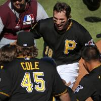 Photo - Pittsburgh Pirates' Neil Walker (18) is greeted by teammates after hitting a walk-off solo-home run off Chicago Cubs relief pitcher Carlos Villanueva during the tenth inning of a baseball game in Pittsburgh Monday, March 31, 2014. The Pirates won 1-0 in ten innings.(AP Photo/Gene J. Puskar)
