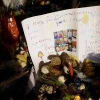 Photo - A poster written by children with the faces of some of the victims is among the many tributes at a memorial to the shooting victims in the Sandy Hook village of Newtown, Conn., Thursday, Dec. 20, 2012.   Adam Lanza walked into Sandy Hook Elementary School in Newtown,  Dec. 14, and opened fire, killing 26 people, including 20 children, before killing himself.(AP Photo/Seth Wenig)