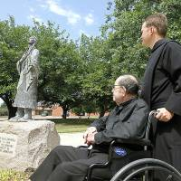 Photo - Father Matthew J. Brown, O.S.B., seated, and Reverand Br. Simeon Spitz, O.S.B., look at a statue of St. Kateri Tekakwitha, the first American Indian saint, on the grounds of St. Gregory's Abbey in Shawnee, OK, Friday, July 5, 2013,  Photo by Paul Hellstern, The Oklahoman
