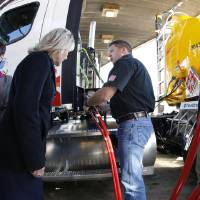 Photo - Gov. Mary Fallin, left, watches as Gemini Motor Transport driver Robert Felts demonstrate how to fill his truck with compressed natural gas.