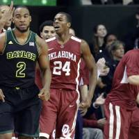 Photo - Oklahoma's Buddy Hield (24) reacts after he scored a 3-pointer as Baylor forward Rico Gathers (2) heads back up court during the second half of an NCAA college basketball game Saturday, Jan. 18, 2014, in Waco, Texas. Oklahoma won 66-64. (AP Photo/LM Otero)