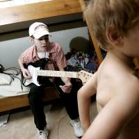 Photo - JARED BLALOCK: Josh Blalock, 17, sits on his bed and plays his guitar as his youngest brother Jared, 4, passes through the room at their family's home in Choctaw, Okla., on Sunday, August 12, 2007. Blalock has cystic fibrosis. By John Clanton, The Oklahoman ORG XMIT: KOD