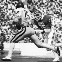 Photo - University of Oklahoma defenseman Kevin Murphy (39) chases down (and subsequently sacks) West Virginia quarterback Jeff Hostetler (15) during game action in Norman.   West Virginia topped the Sooners by a 41-27 score. Staff photo by Jim Argo taken 9/11/82. File:  College Football/OU/OU-West Virginia/Kevin Murphy/1982