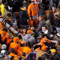 Photo -  A stretcher is passed down to the field as Oklahoma State's Brandon Weeden (3) makes his way out of the crowd following the Bedlam college football game between the Oklahoma State University Cowboys and the University of Oklahoma Sooners at Boone Pickens Stadium in Stillwater, Okla., Saturday, Dec. 3, 2011. Photo by Bryan Terry, The Oklahoman