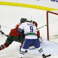 Photo - Vancouver Canucks' Chris Higgins, left top, watches his power-play goal off Minnesota Wild goalie Niklas Backstrom, of Finland, in the first period of an NHL hockey game on Thursday, Feb. 7, 2013, in St. Paul, Minn. (AP Photo/Jim Mone)