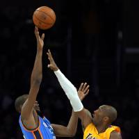 Photo - Oklahoma City Thunder forward Kevin Durant, left, shoots over Los Angeles Lakers guard Kobe Bryant during the first half of their NBA basketball game, Friday, Jan. 11, 2013, in Los Angeles. (AP Photo/Mark J. Terrill)