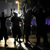 Photo - People raise their hands in the middle of the street as police wearing riot gear move toward their position trying to get them to disperse Monday, Aug. 11, 2014, in Ferguson, Mo. The FBI opened an investigation Monday into the death of 18-year-old Michael Brown, who police said was shot multiple times Saturday after being confronted by an officer in Ferguson. Authorities in Ferguson used tear gas and rubber bullets to try to disperse a large crowd Monday night that had gathered at the site of a burned-out convenience store damaged a night earlier, when many businesses in the area were looted. (AP Photo/Jeff Roberson)