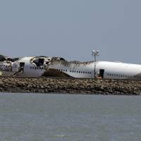 Photo - The wreckage of Asiana Flight 214, which crashed on Saturday, July 6, 2013, is seen on a tarmac at San Francisco International Airport in San Francisco, Tuesday, July 9, 2013. (AP Photo/Jeff Chiu)
