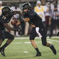 Photo - Vanderbilt quarterback Patton Robinette, right, hands off the ball to running back Ralph Webb (26) in the first quarter of an NCAA college football game against Temple on Thursday, Aug. 28, 2014, in Nashville, Tenn. (AP Photo/Brian Powers)