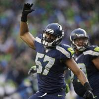 Photo - Seattle Seahawks linebacker Mike Morgan (57) celebrates after New Orleans Saints kicker Shayne Graham missed a 48-yard field goal during the fourth quarter of an NFC divisional playoff NFL football game in Seattle, Saturday, Jan. 11, 2014. (AP Photo/Elaine Thompson)