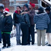 Photo - Friends and family members console each other, Tuesday, Dec. 25, 2012 in Flint, Mich. Michigan authorities say five people are dead in two separate incidents of what is believed to be accidental carbon monoxide poisoning. (AP Photo/Flint Journal, Griffin Moores)