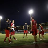 Photo - In this photo taken Dec. 29, 2012, baseball players warm up prior to a game in Caguas, Puerto Rico. On an island where the name of Roberto Clemente is emblazoned on stadiums, streets and schools, the sport of baseball is poised to make a late-inning rally. In the past year, Major League Baseball reported the second-highest number of signings from Puerto Rico since the year 2000. (AP Photo/Ricardo Arduengo)