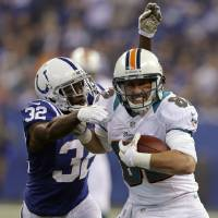Photo - FILE - In this Nov. 4, 2012 file photo, Miami Dolphins wide receiver Brian Hartline, right, tries to break the tackle of Indianapolis Colts cornerback Cassius Vaughn during the first half of an NFL football game in Indianapolis. The veteran receiver agreed to a five-year deal for nearly $31 million to remain with the Miami Dolphins, his agent said Friday, March 8, 2013.  (AP Photo/Darron Cummings, File)