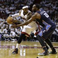 Photo - Charlotte Bobcats' Al Jefferson (25) defends Miami Heat's LeBron James during the first half in Game 2 of an opening-round NBA basketball playoff series, Wednesday, April 23, 2014, in Miami. (AP Photo/Lynne Sladky)