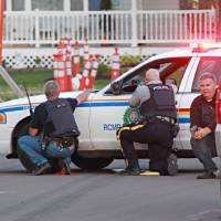 Photo - Police officers take cover behind their vehicles in Moncton, New Brunswick, on Wednesday June 4, 2014. Three police officers were shot dead and two others injured Wednesday in the east coast Canadian province of New Brunswick, officials said, and authorities were searching for a suspect. (AP Photo/Moncton Times & Transcript, Ron Ward via The Canadian Press ) MANDITORY CREDIT
