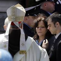 Photo - Boston Cardinal Sean O'Malley comforts Patty Campbell and her son, Billy, after a  funeral for her daugher, Krystle Campbell, 29, at St. Joseph's Church in Medford, Mass. Monday, April 22, 2013. Krystle Campbell is one of three victims killed in the Boston Marathon explosions. (AP Photo/Elise Amendola)