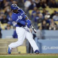 Photo - Los Angeles Dodgers' Hanley Ramirez hits a solo home run against the Los Angeles Angels during the third inning of an exhibition baseball game in Los Angeles, Thursday, March 27, 2014. (AP Photo/Danny Moloshok)