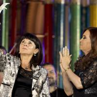 Photo - President Cristina Fernandez, right, applauds as Susana Trimarco, left, lifts a human rights prize given by the president during a rally to mark the 29th anniversary of the return to democracy in Argentina, on the eve of the Human Rights Day, in Buenos Aires, Argentina,  Sunday, Dec. 9, 2012. Trimarco is known for her crusade to find her daughter, Maria de los Angeles