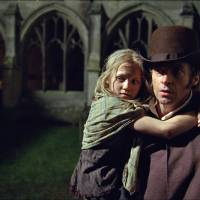 Photo - This film image released by Universal Pictures shows Hugh Jackman as Jean Valjean holding Isabelle Allen as Young Cosette in a scene from
