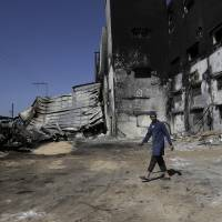 Photo - Ahmad Baraka, 25, a Palestinian worker at Al Awda snack food factory inspects the damage and burned factory in Deir el-Balah, central Gaza Strip. The factory owner, Mohammed al-Telbani, lost his life's work during the Gaza war after Israeli shells slammed into his four-story factory, one of Gaza's largest, sparking a fire that engulfed vats of margarine and sacks of cocoa powder. Al-Telbani and others in Gaza say anything short of a complete opening of Gaza's borders, after seven years of closure by Israel and Egypt, will do little to change their lives. (AP Photo/Adel Hana)
