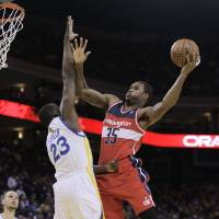 Photo - Washington Wizards' Trevor Booker, right, shoots over Golden State Warriors' Draymond Green (23) during the first half of an NBA basketball game, Tuesday, Jan. 28, 2014, in Oakland, Calif. (AP Photo/Ben Margot)
