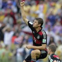 Photo - Germany's Thomas Mueller celebrates scoring the opening goal during the group G World Cup soccer match between the USA and Germany at the Arena Pernambuco in Recife, Brazil, Thursday, June 26, 2014. (AP Photo/Matthias Schrader)