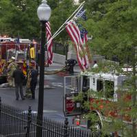 Photo - District of Columbia Fire department trucks and personnel are seen parked between the The Eisenhower Executive Office Building and the West Wing as they respond to a call at the White House, Saturday, May 11, 2013, in Washington. The West Wing including the media area were evacuated because of smoke according to Secret Service Uniformed Division. Journalists were sent outside shortly after 7 a.m. while firefighters inspected the West Wing. They were allowed back into the building about an hour later. (AP Photo/Carolyn Kaster)