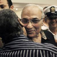 Photo -   FILE - In this Friday, June 8, 2012 file photo, Egyptian presidential runoff candidate Ahmed Shafiq is greeted by a supporter after attending a press conference in Cairo, Egypt. Shafiq's candidacy has dismayed many Egyptians who believe the veteran figure of Mubarak's regime will only preserve the authoritarianism of his rule. But even if some Christians share those reservations, they view his opponent in the race as far worse: Mohammed Morsi, of the Muslim Brotherhood, which Egypt's Christian minority fears will turn the country into an Islamic state. (AP Photo/Nasser Nasser, File)