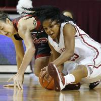 Photo - Oklahoma's Gioya Carter, right, gains control of the ball beside Louisville's Megan Deines during the first half of an NCAA college basketball game in Norman, Okla., Sunday, Nov. 17, 2013. (AP Photo/Bryan Terry)